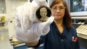Teresita Gatmaitan, a die setter at the United States Mint at San Francisco, holds a finished 2016 Ronald Reagan Presidential $1 proof coin.