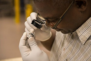 West Point Coin Production Supervisor, Jeff Odom inspects a newly struck 2014 Platinum Proof Coin.