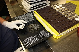 West Point production staff hand-fitting encapsulated coins into the presentation case for the  2014 American Eagle Platinum Proof Coin.