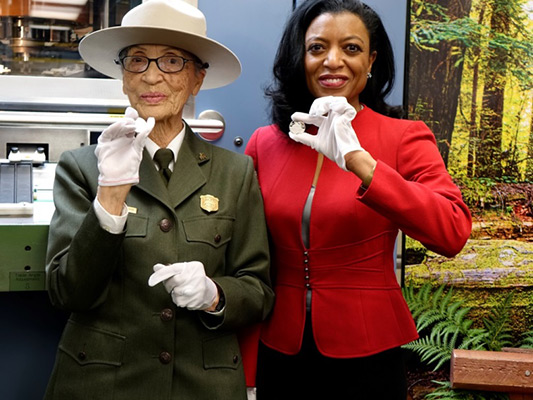 Park Ranger Betty Soskin and United States Mint Chief of Staff Elisa Basnight show off newly struck coins to the invited guests, local media and employees.