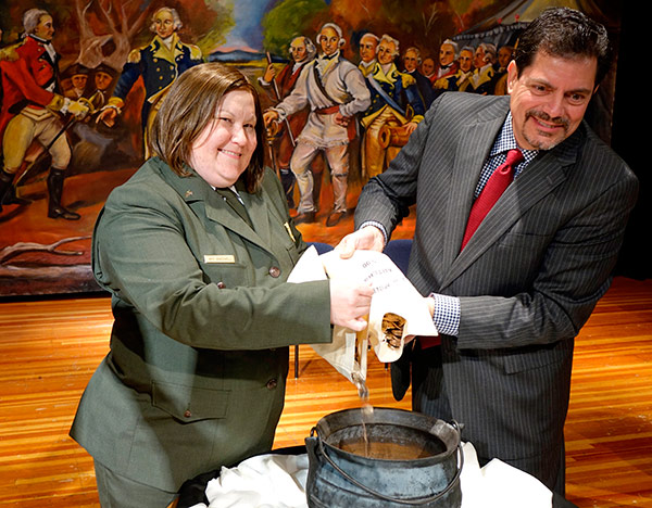Superintendent Amy Bracewell and Acting Quality Manager Ron Harrigal pour new Saratoga National Park quarters into an old kettle.