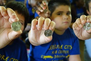 Children hold up their new Everglades National Park quarters.