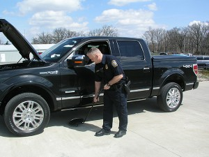 Mint Police Officer Mark Campbell, assigned to the Protection Division of the U.S. Bullion Depository at Fort Knox, Kentucky, conducts a vehicle security inspection.