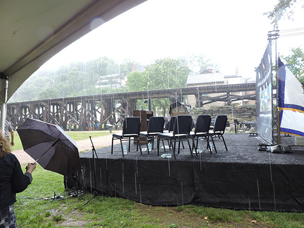A sudden downpour sends audience running for cover. The ceremony resumed after the storm passed.