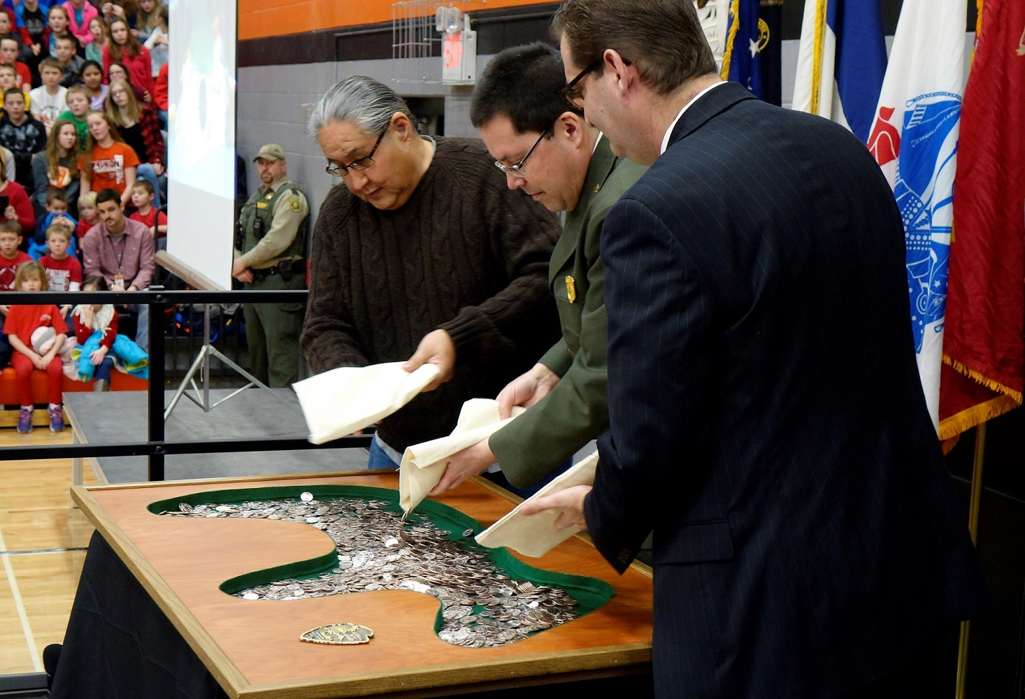 Chairman Edmore Green, Superintendent Jim Nepstad, and U.S. Mint Plant Superintendent Marc Landry pour coins during the launch of the Effigy Mounds National Monument quarter in Waukon, Iowa. U.S. Mint photo by Jill Westeyn.