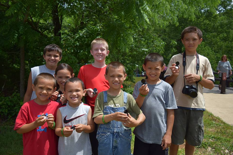 Kids proudly hold their new Ozark National Scenic Riverways quarters after the launch ceremony.