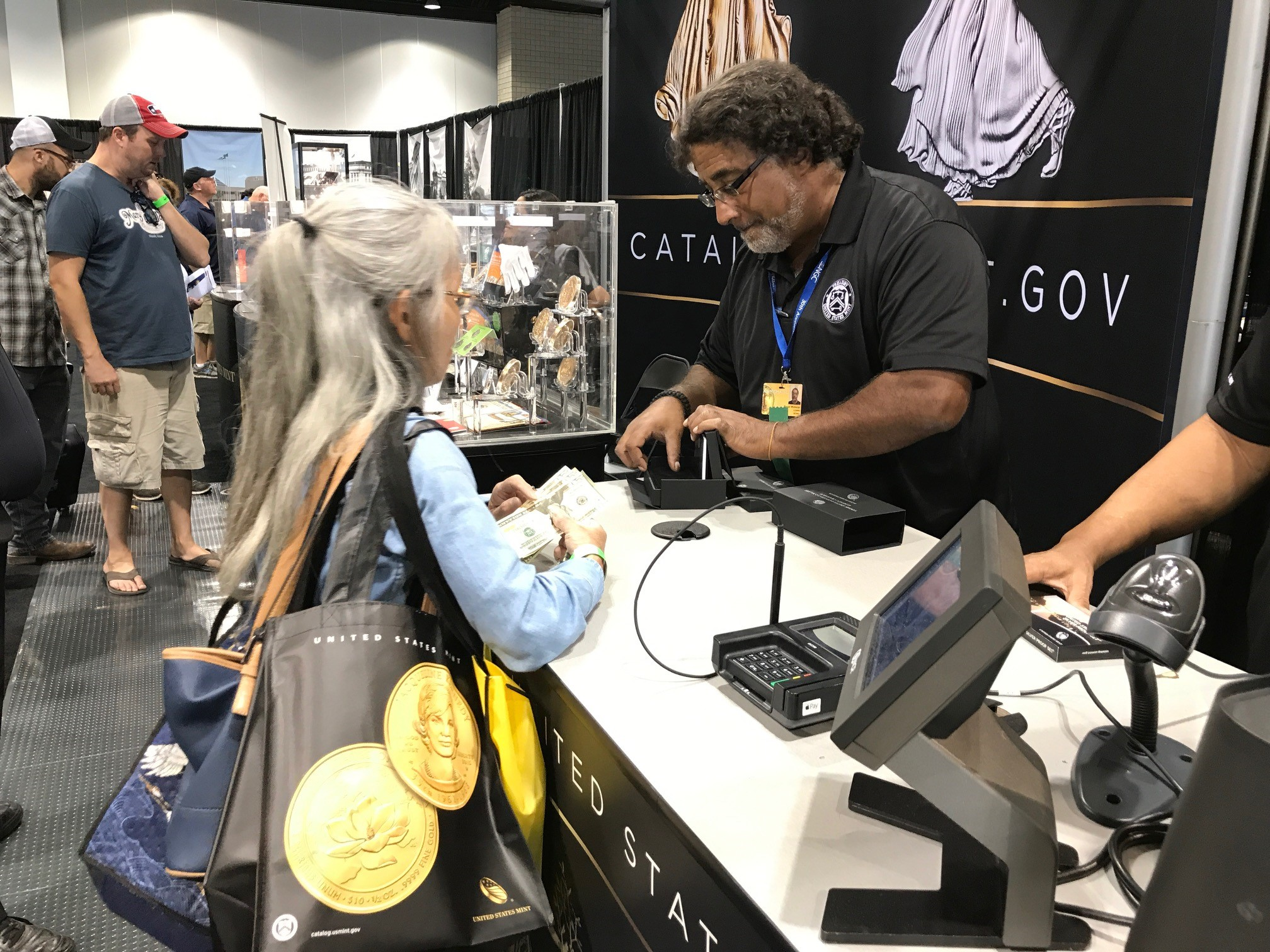 A customer makes a purchase from the U.S. Mint at booth #478. U.S. Mint photo by Debbie Dawson.