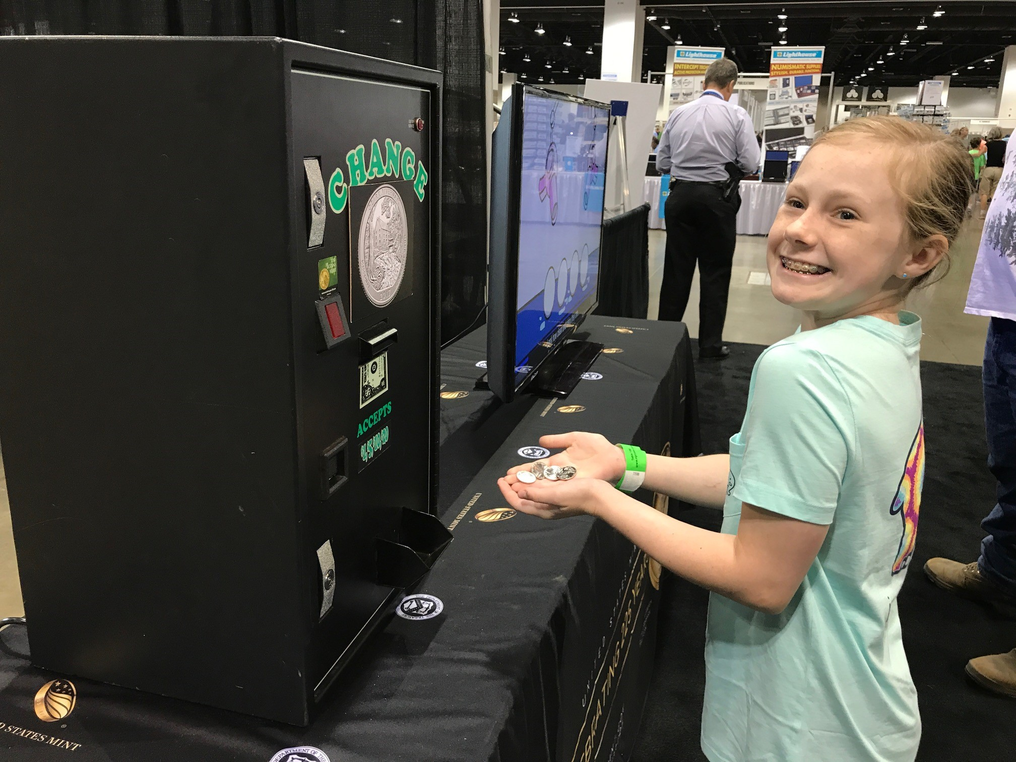 A youngster exchanges cash for Ozark quarters. U.S. Mint photo by Debbie Dawson.