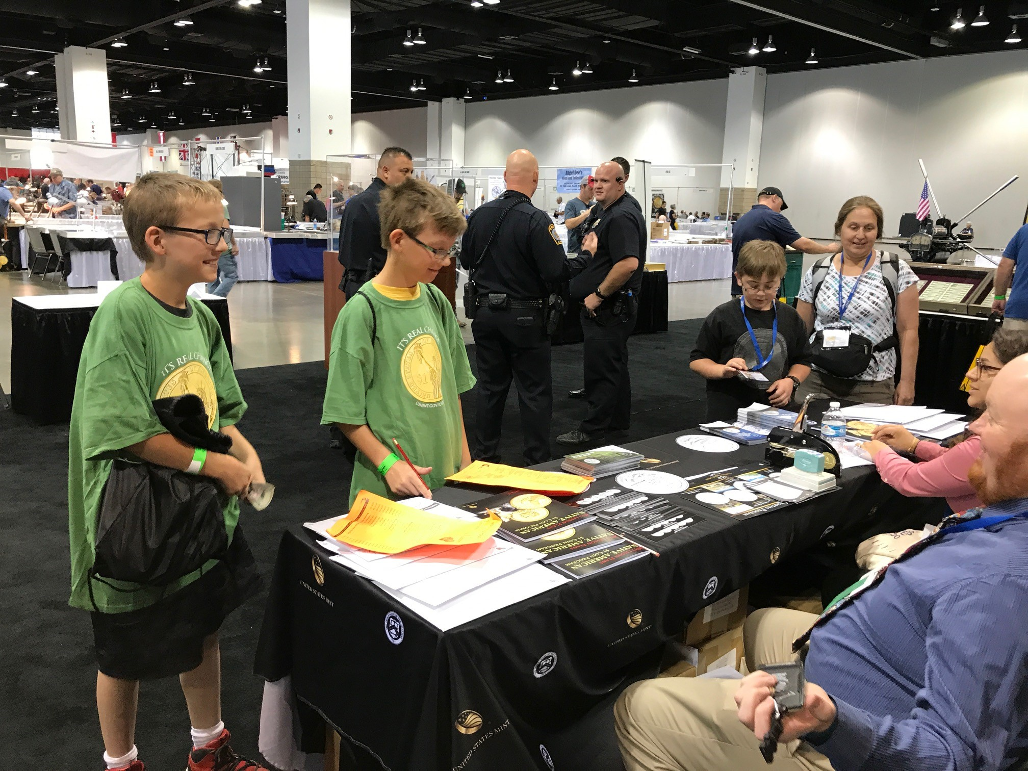 Young numismatists pick up a treasure map to use on the bourse floor. U.S. Mint photo by Debbie Dawson.