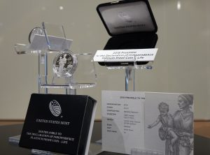 black and silver packaging, a platinum proof coin, and line art showing liberty holding a child