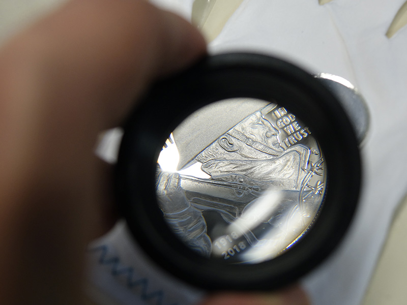 A newly-minted World War I Centennial Silver Dollar seen through a magnifying lens