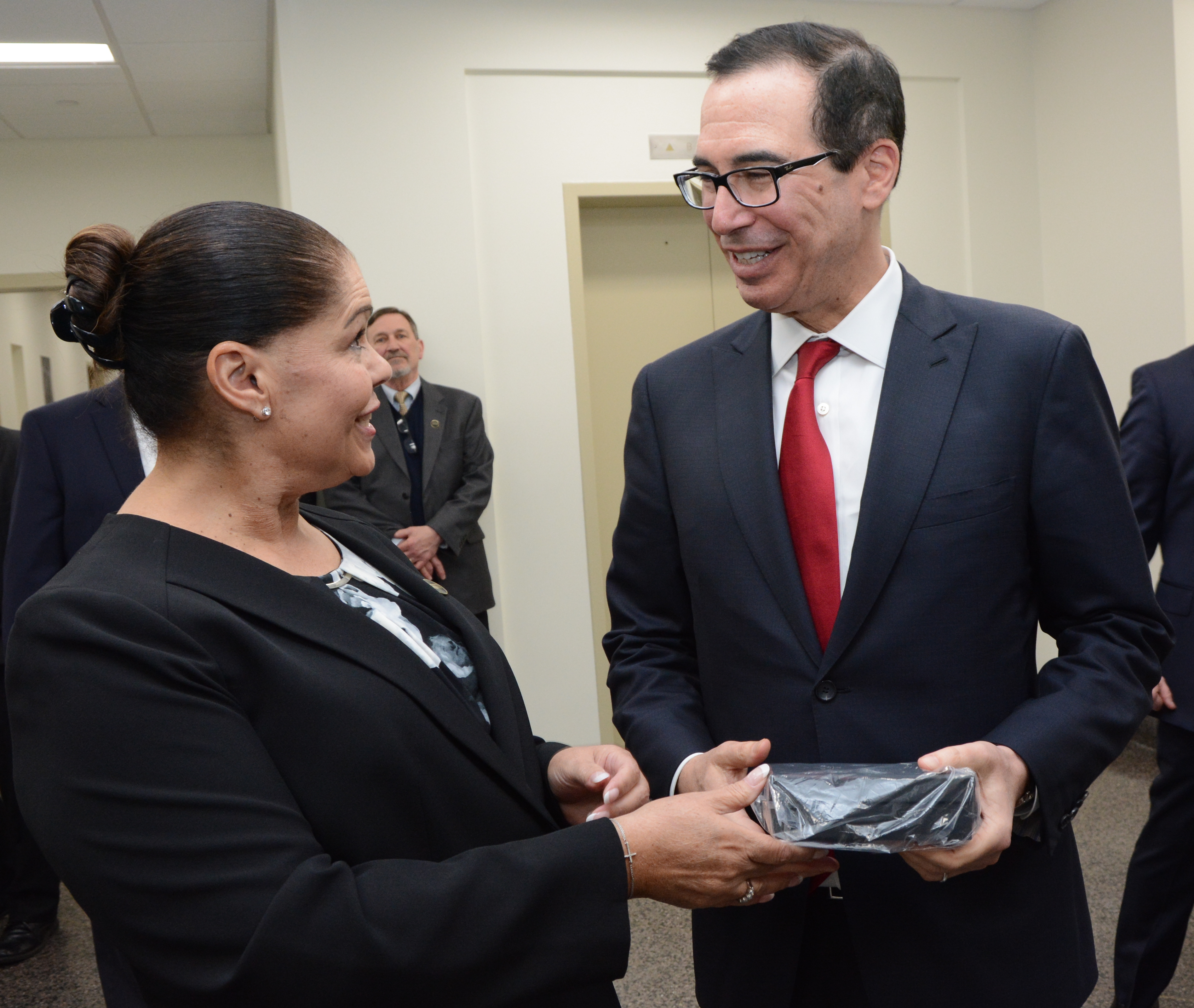 U.S. Mint Acting Superintendent (Philadelphia facility) Laurie Johnson presents Treasury Secretary Steven Mnuchin with the World War I Centennial 2018 Proof Silver Dollar he struck during a tour of the numismatic room at the U.S. Mint facility in Philadel