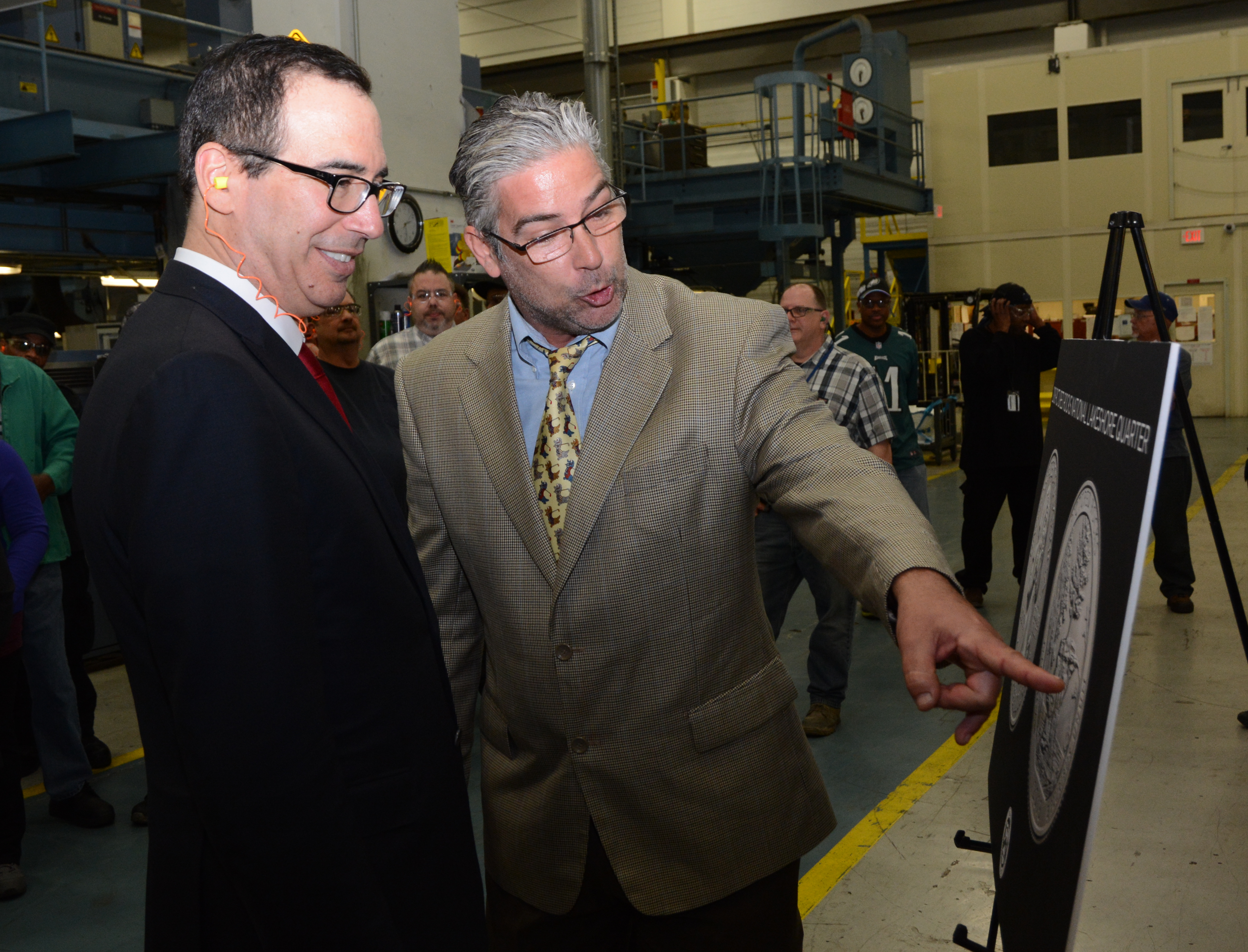 Michael Gaudioso, U.S. Mint Sculptor-Engraver of the Pictured Rocks National Lakeshore quarter, discusses his work on the coin with Treasury Secretary Steven Mnuchin during a tour of the circulating production area at the U.S. Mint facility in Philadelphi