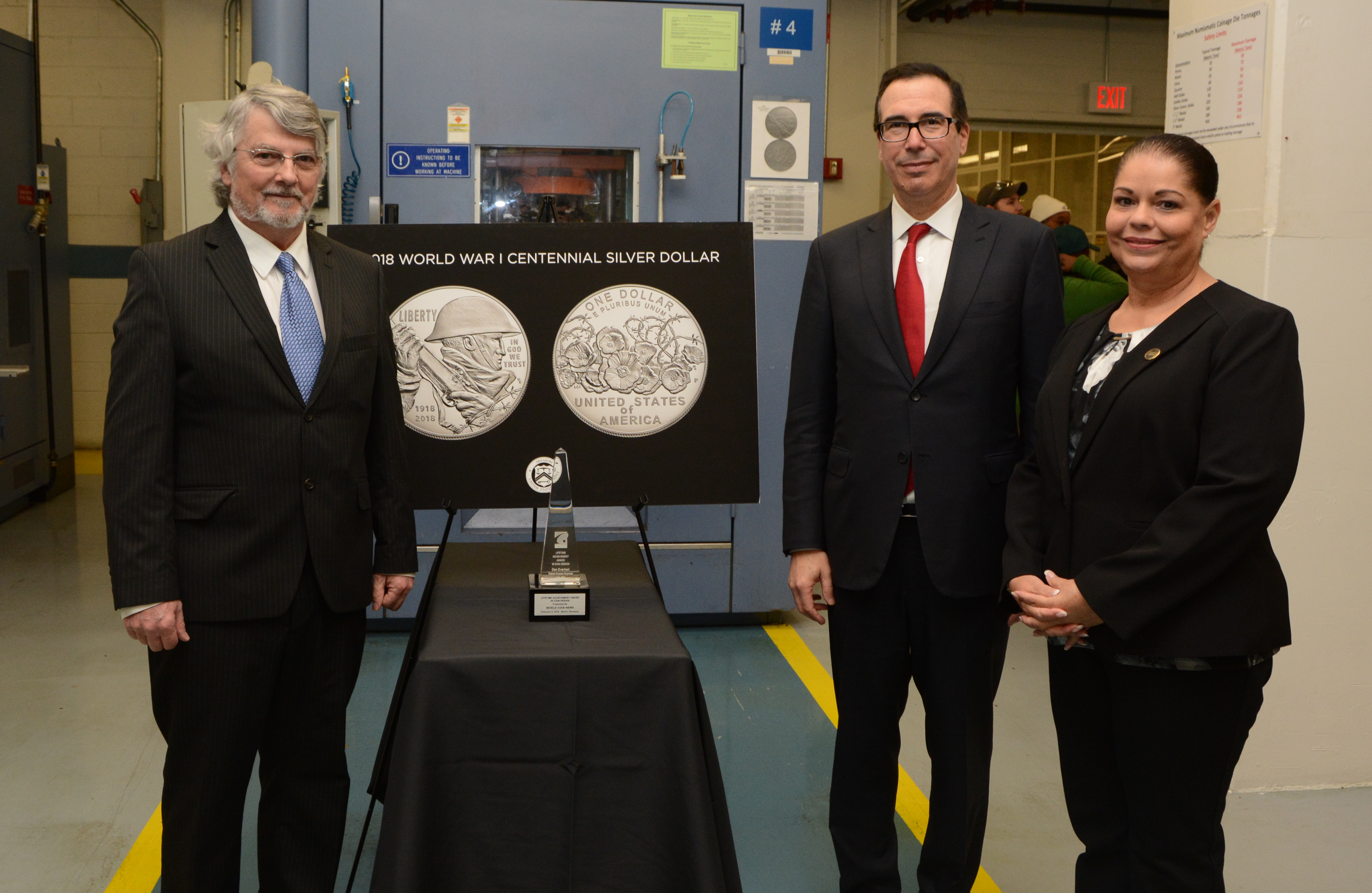 Treasury Secretary Steven Mnuchin, U.S. Mint Acting Superintendent (Philadelphia facility) Laurie Johnson, and retired U.S. Mint Sculptor-Engraver Don Everhart pose for a photo during a tour of the numismatic room at the U.S. Mint facility in Philadelphia
