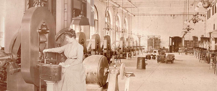 historic photo of a woman operating a coin press
