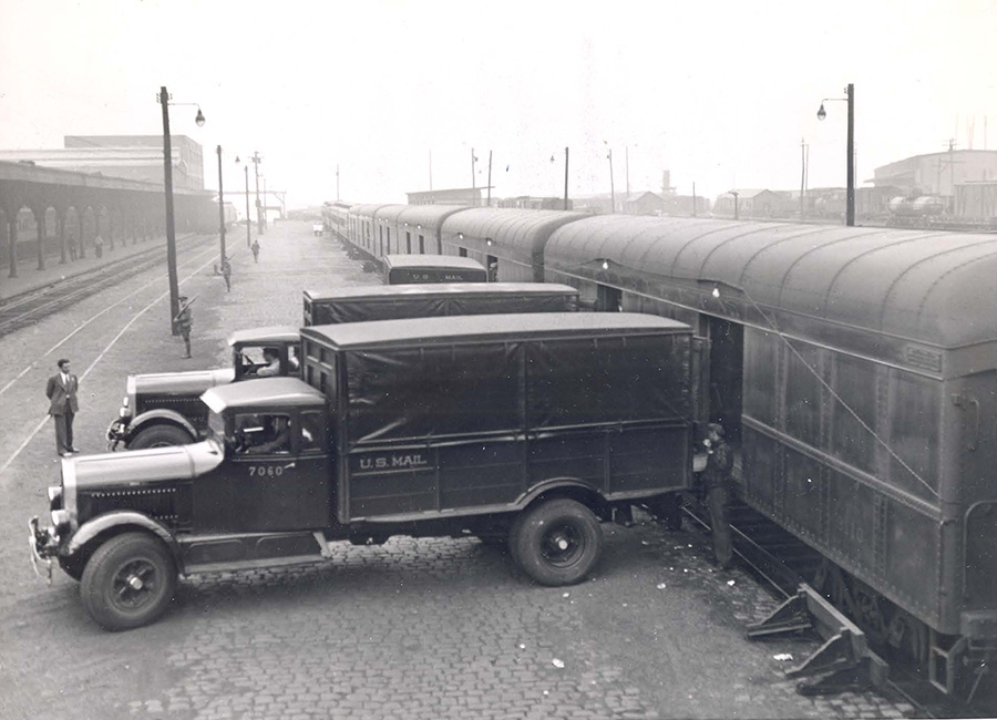 Trucks holding gold bullion being loaded into railroad cars.