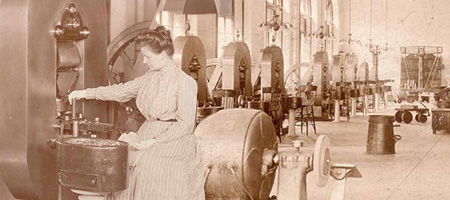 woman feeding blanks into a coin press with coin presses lined up behind her