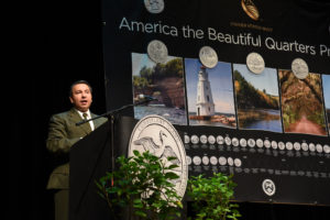 National Park Service employee stands at a podium in front of an ATB banner