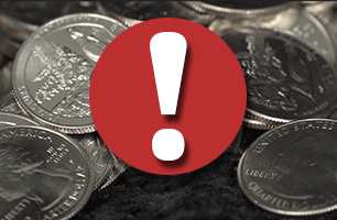 white exclamation point in a red circle in front of pile of quarters