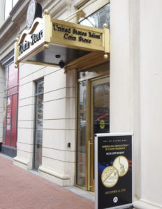 door to the United States Mint Coin Store with sign in front announcing the American Innovation $1 Coin Program kick off event.