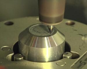 machine engraving the design onto the master hub